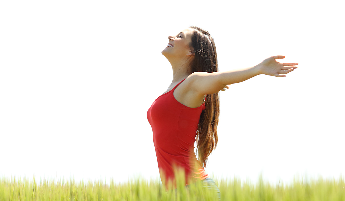 woman standing in a field taking a big deep breath after her salt therapy