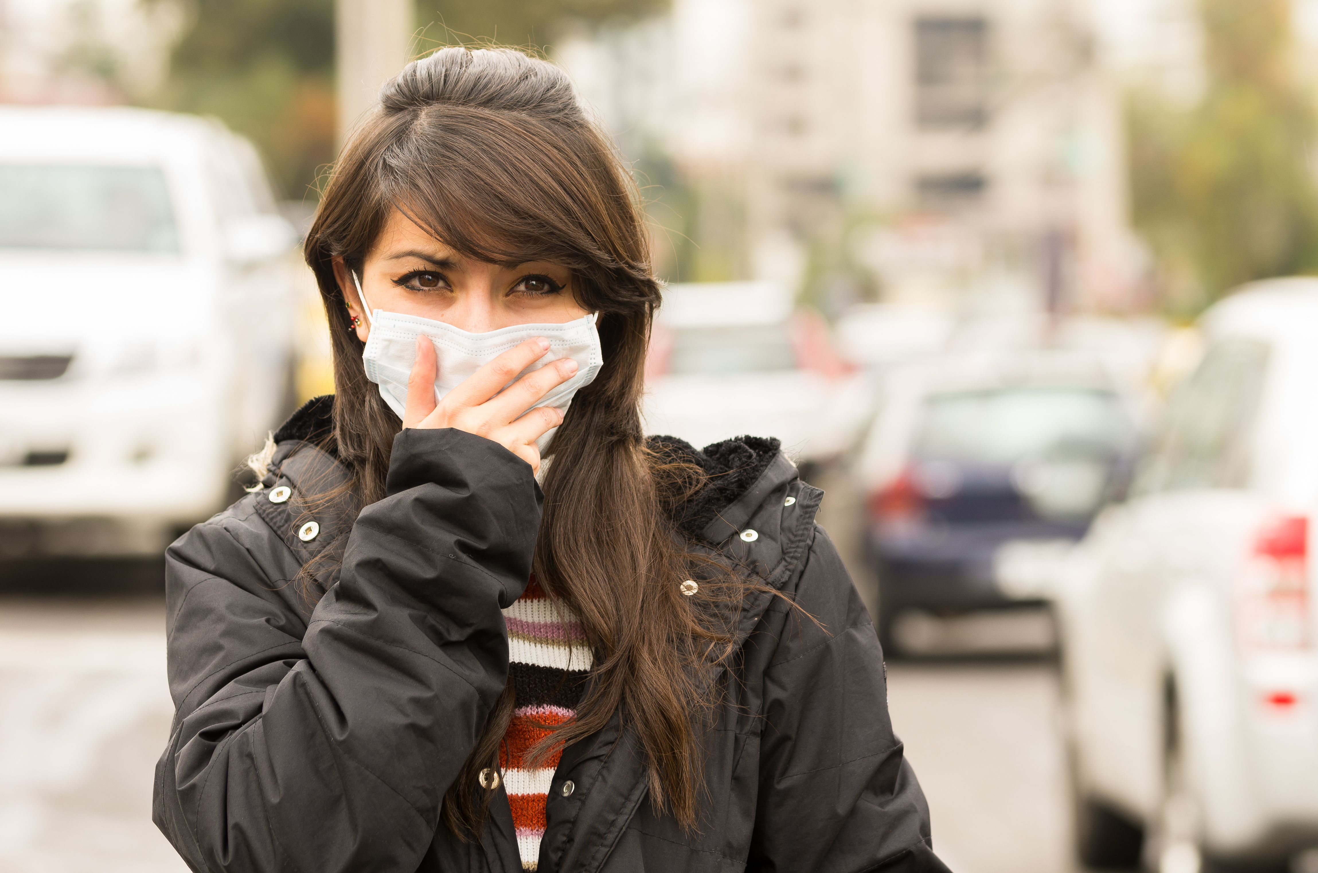a woman covering her mouth with a breathing mask due to the high level of air pollution
