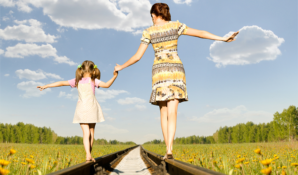 Mother and daughter walking along some train tracks feeling happy and healthy